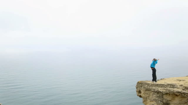 young woman on a cliff above the sea