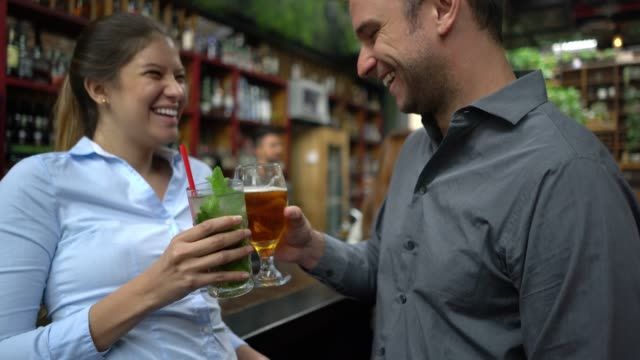 young woman on a date with a handsome man enjoying beer and a mojito both flirting - bar area stock videos & royalty-free footage