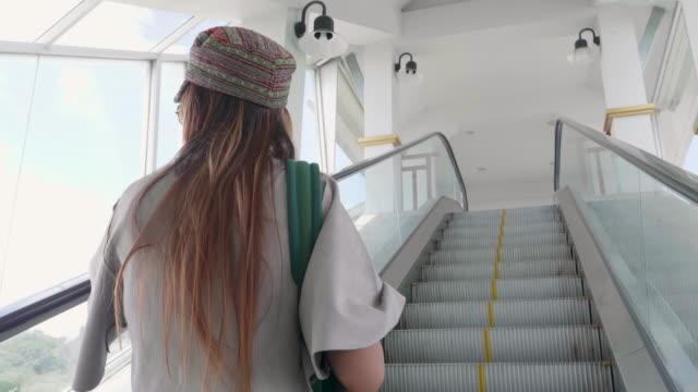 young woman on a moving escalator - steps and staircases stock videos & royalty-free footage