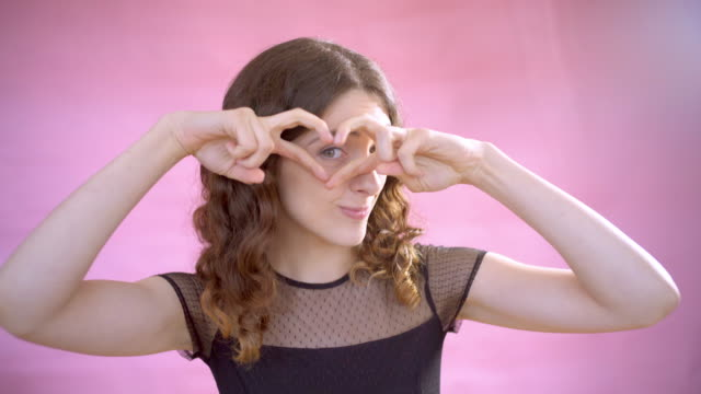 stockvideo's en b-roll-footage met a young woman on a pink background. - roze achtergrond