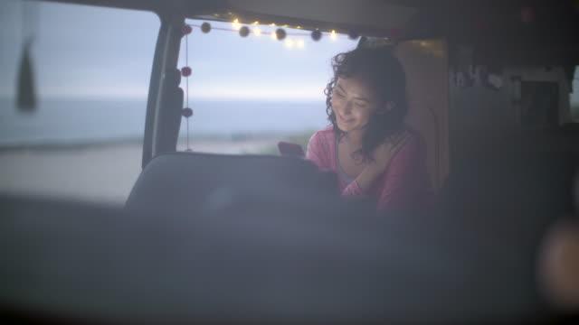 vídeos de stock e filmes b-roll de young woman on a road trip in her camper van - viagem em estrada