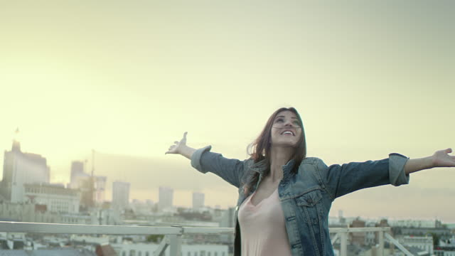 young woman on a rooftop. enjoying freedom - happiness stock videos & royalty-free footage