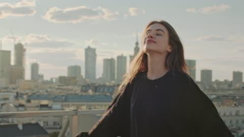 vídeos y material grabado en eventos de stock de una joven en un tejado. brazos abiertos - tejado
