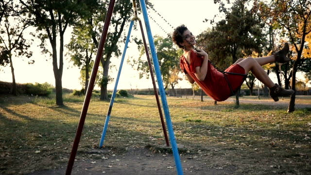 young woman on a swing in a park - swinging stock videos & royalty-free footage