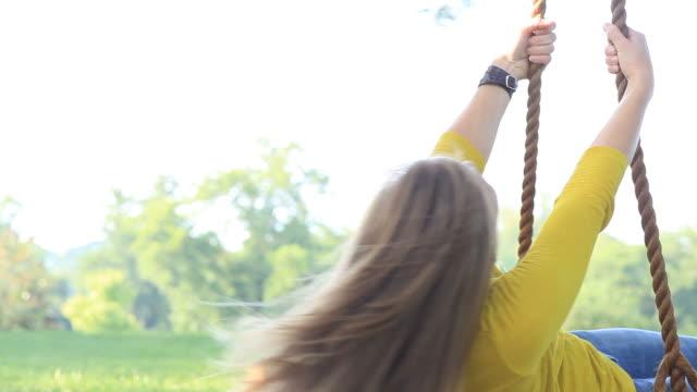 若い女性は、ブランコにします。 - ブランコ点の映像素材/bロール