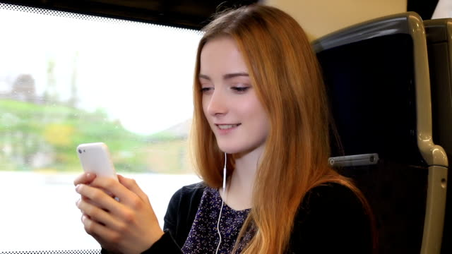 Young woman on a train listening to music.
