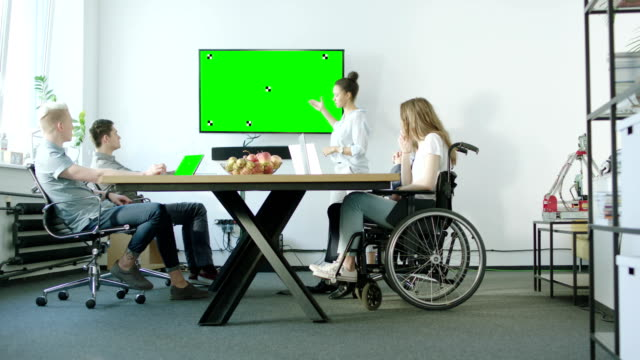 Young woman on a wheelchair and her presenting team discussing with their mentor. Startup company