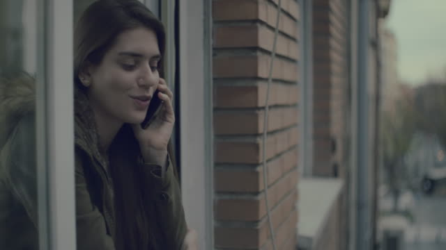 Young woman on a window talking on the phone.