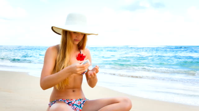 young woman on beach - sun cream stock videos and b-roll footage