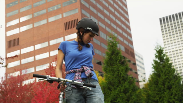 ms young woman on bicycle using mobile phone with city in background / portland, oregon, usa - cycling helmet stock videos & royalty-free footage