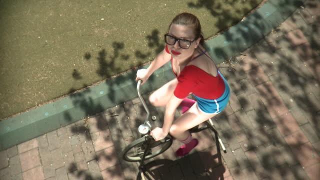 ws ha young woman on exercise bike in park, new york city, new york, usa - 口を尖らせる点の映像素材/bロール
