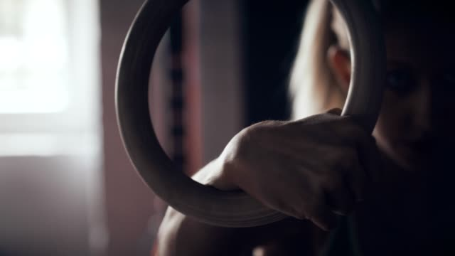 Young woman on gym rings