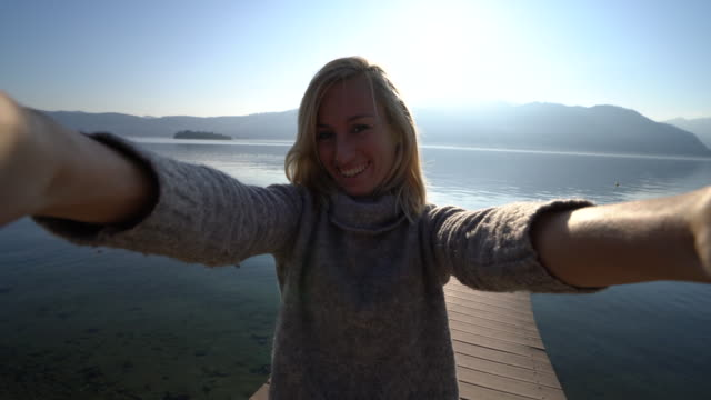 Young woman on jetty above lake, takes selfie portrait