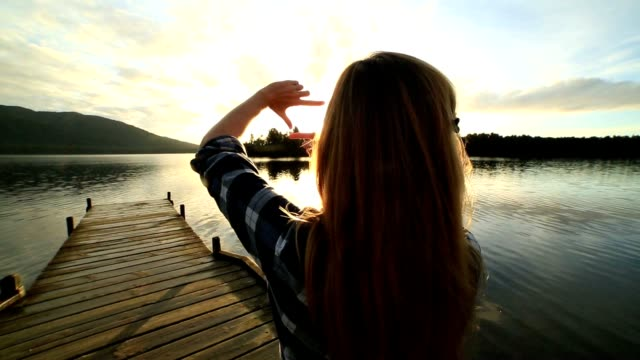 Young woman on lake pier makes hand finger frame on landscape