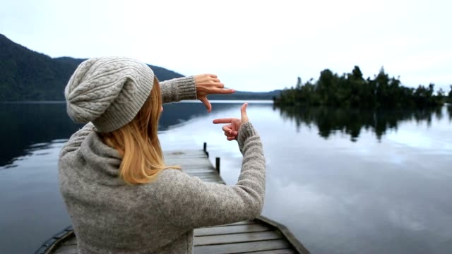young woman on lake pier makes hand finger frame on landscape - content stock videos & royalty-free footage