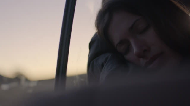 cu. young woman on long car ride wakes up from nap and smiles. - kopfkissen stock-videos und b-roll-filmmaterial