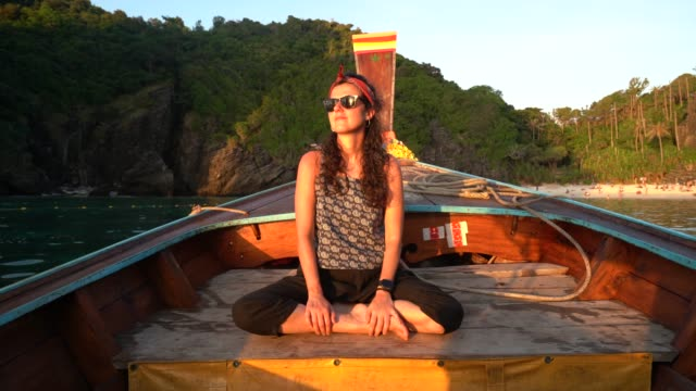 young woman on longtail boat at sunset in thailand, phi phi island - phi phi islands stock videos & royalty-free footage