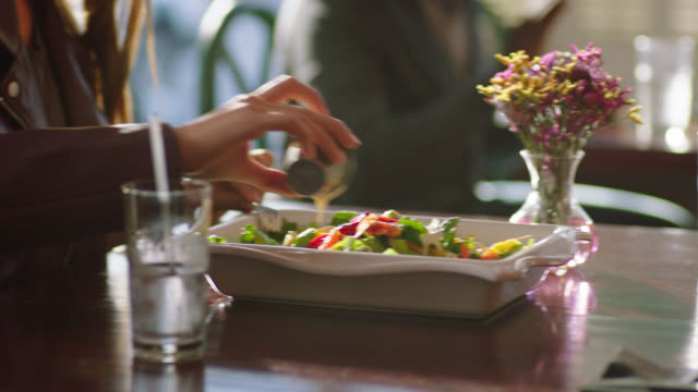 young woman on lunch date drizzles salad dressing over salad and shares plate with partner. - salad dressing stock videos & royalty-free footage
