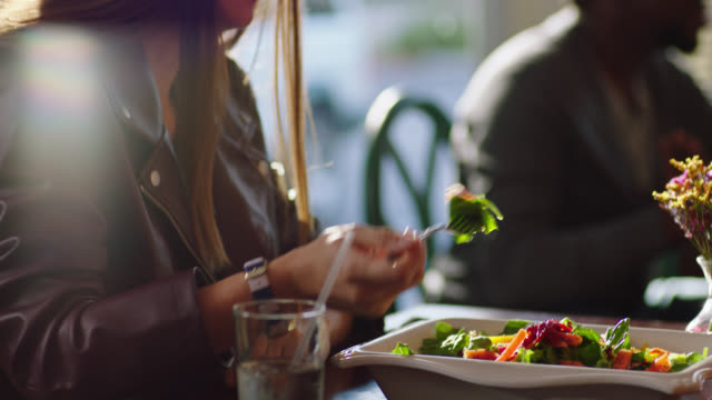 Young woman on lunch date feeds a bite of salad to her partner.