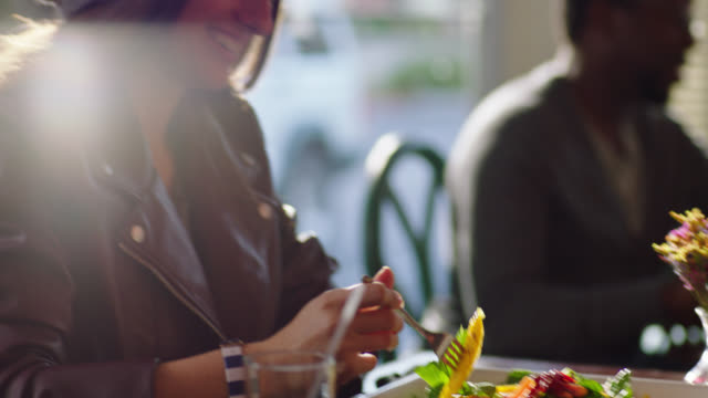Young woman on lunch date takes a bite of salad.