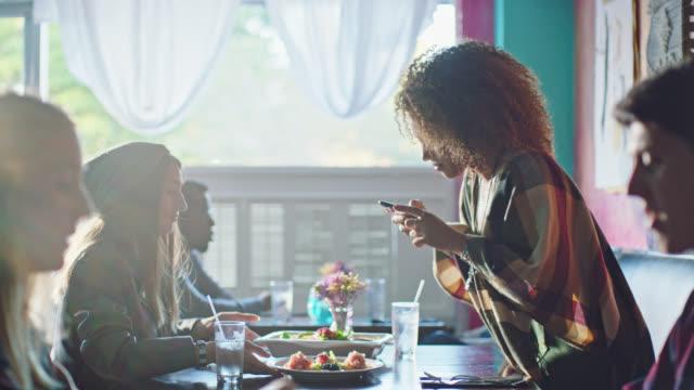 young woman on lunch date takes smartphone photos of food plates at local restaurant. - bild bildbanksvideor och videomaterial från bakom kulisserna
