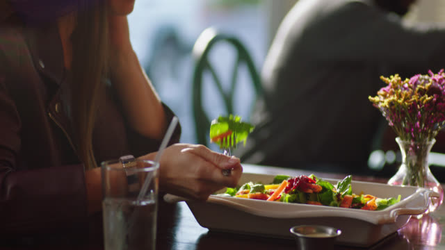 Young woman on lunch date tries a bite of salad and recommends it to her partner.