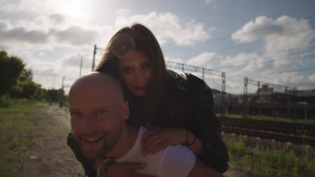 young woman on man's back. rock and roll style. - bracelet stock videos and b-roll footage
