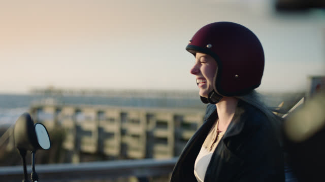 ms. young woman on motorcycle laughs with friend as ocean breeze blows her hair. - helmet motorcycle stock videos and b-roll footage