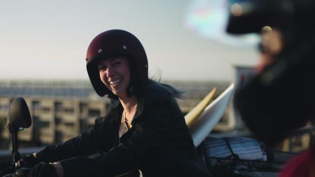vídeos y material grabado en eventos de stock de ms slo mo. young woman on motorcycle laughs with friend by seaside pier. - manillar