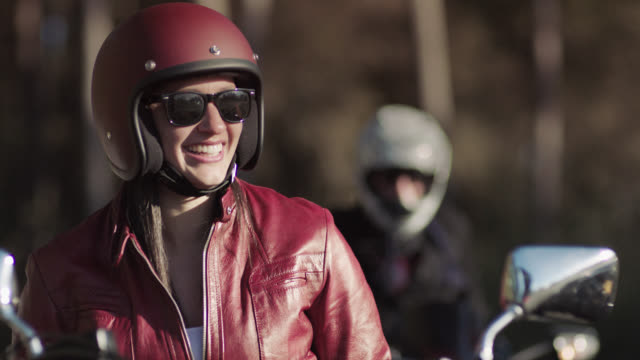 slo mo. young woman on motorcycle laughs with friends in biker club. - ヘルメット点の映像素材/bロール