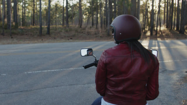 SLO MO. Young woman on motorcycle sits at crossroads and wonders which way to go.