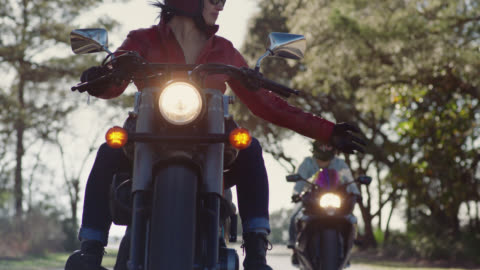 stockvideo's en b-roll-footage met slo mo. young woman on motorcycle waves for her friends to pass her on sunny forest drive. - waving