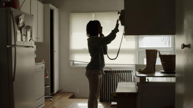 ws young woman on phone in kitchen / provo, utah, usa - provo bildbanksvideor och videomaterial från bakom kulisserna