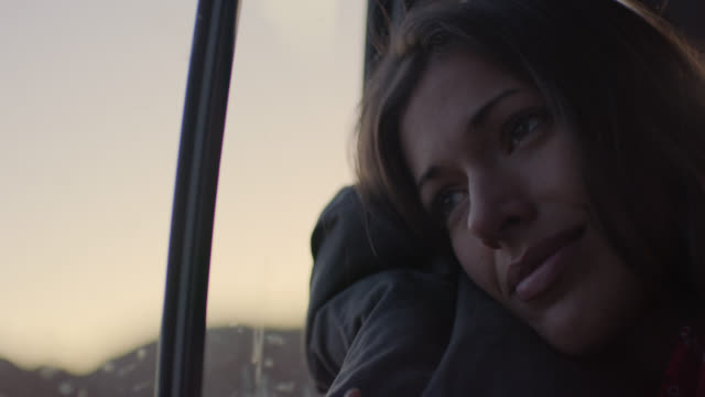 vidéos et rushes de cu. young woman on road trip leans head on pillow and looks out car window. - contemplation