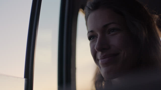 stockvideo's en b-roll-footage met cu. young woman on road trip rides with the window down and smiles as she waves her hand in the open air. - ontdekkingsreiziger