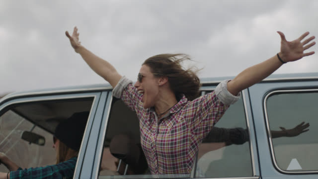 SLO MO. Young woman on road trip with friends raises arms and cheers from open car window.