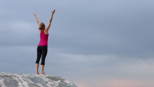 ws young woman on rock ledge doing yoga salutations arms outstretched/singapore - human limb stock videos and b-roll footage
