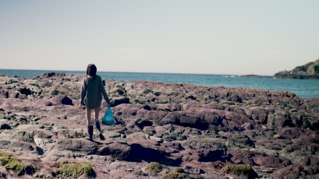 young woman on rocky sea coastline in gum boots with bag - kingsand video stock e b–roll