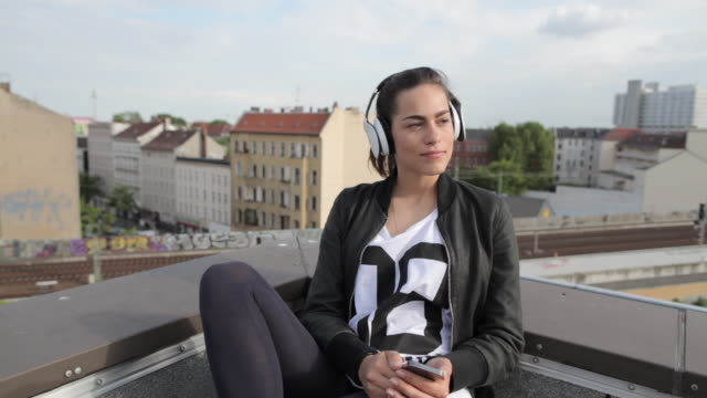 Young woman on rooftop in Berlin, Germany selecting music on smartphone and listening with headphones.