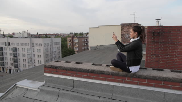 vídeos y material grabado en eventos de stock de young woman on rooftop in berlin, germany, sitting, taking picture with smartphone. - sentado