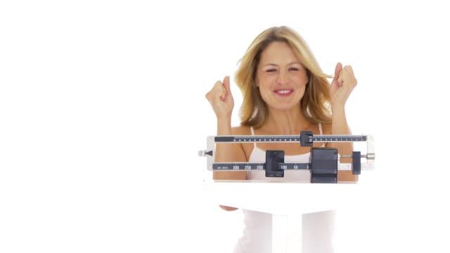 vídeos de stock e filmes b-roll de young woman on scale happy about her weight - só mulheres de idade mediana