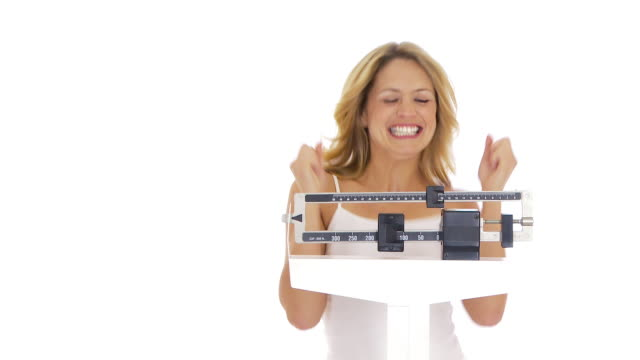 Young woman on scale happy about her weight