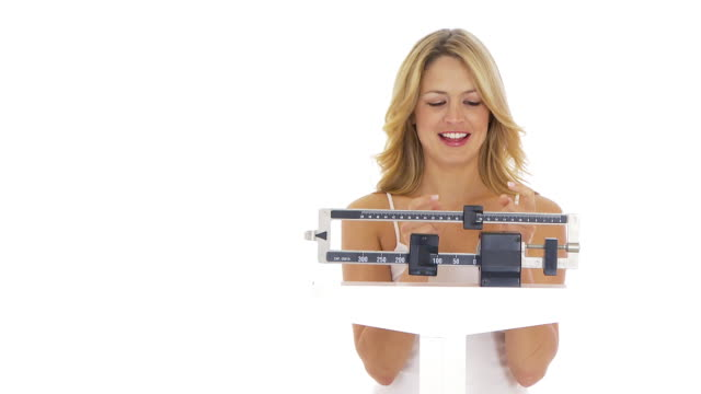 Young woman on scale happy about weight