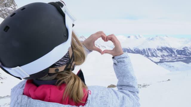 junge frau auf ski pisten machen herzform - ganz oben stock-videos und b-roll-filmmaterial