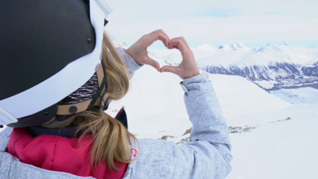young woman on ski slopes making heart shape - conceptual symbol stock videos and b-roll footage