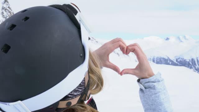 Young woman on ski slopes making heart shape