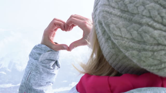 Young woman on ski slopes making heart shape
