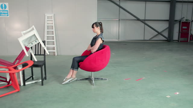 young woman on swivel chair with pile of chairs - chair stock videos & royalty-free footage