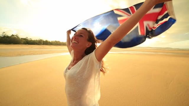 Young woman on the beach at sunset holding an Australian flag in the air