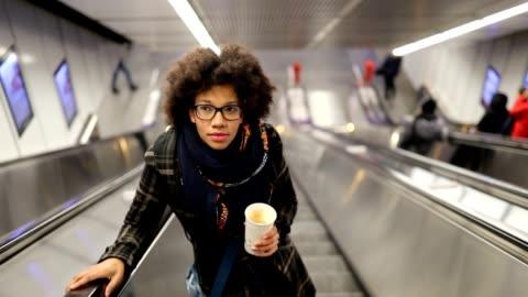 junge frau auf der rolltreppe - kaffee stock-videos und b-roll-filmmaterial